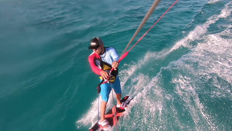 Action camera footage of a kitesurfer doing the release trick, jumping Live Action