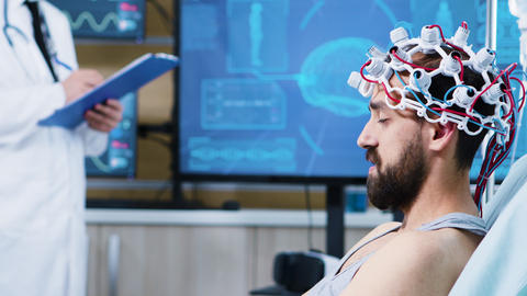 Patient with brainwaves scanning headset sitting on bed ビデオ