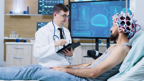 Doctor in brain research staying next to patient bed and typing on tablet GIF