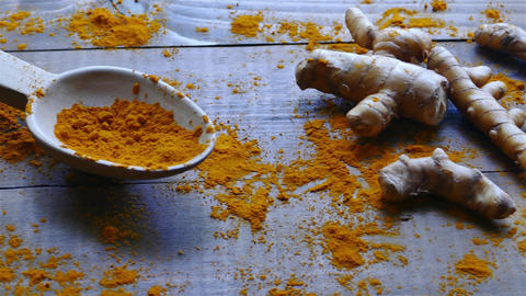 Turmeric roots and powder in wooden spoon on the wooden rustic looking table ビデオ