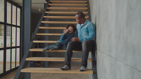 Lovely little boy talking on cellphone on stairs GIF