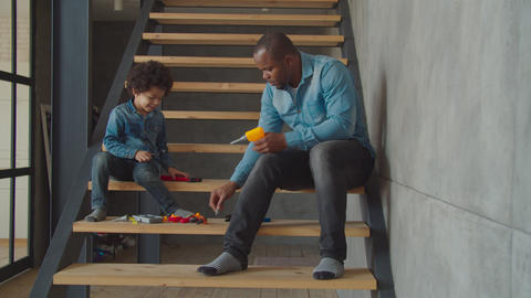 Cute kid with dad playing with toy tools on stairs Archivo