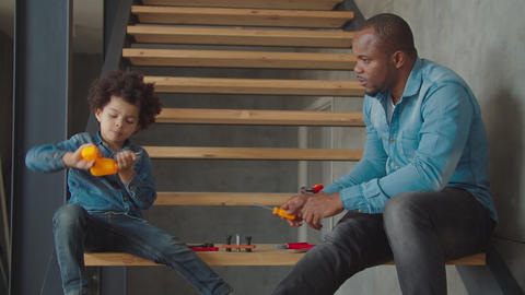 Biracial family with kid learning toy work tools Archivo