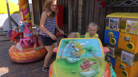 Happy family mother and son with daughter spin on car carousel. Gimbal movement GIF