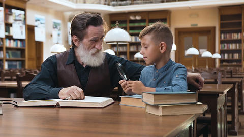 Handsome wise bearded grandfather spending time in library with his teen Archivo