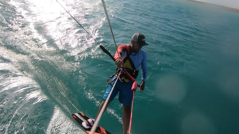 Kite surfer is gliding on water, turning, water splash, view from the slings Live Action