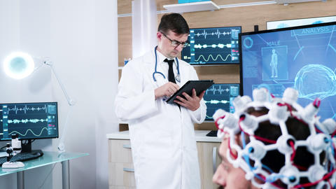 Doctor in a modern neuroscience centre making notes on tablet GIF