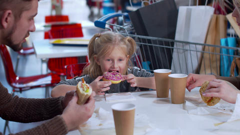 Girl eats a donut in a mall, slow motion Archivo