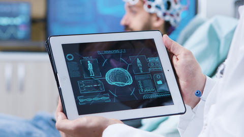 Doctor in a modern clininc holding tablet with brain analysis Live Action