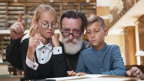 Handsome bearded old man reading book, raised finger that his teenage Archivo