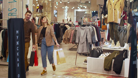 Happy couple walk in a store with packages Archivo