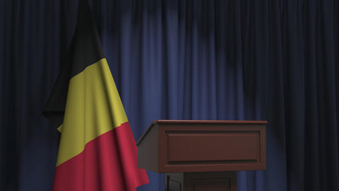 Flag of Belgium and speaker podium tribune. Political event or statement related Live Action