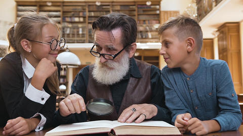 Intelligent old bearded granddad in glasses, reading book with magnifying glass Archivo