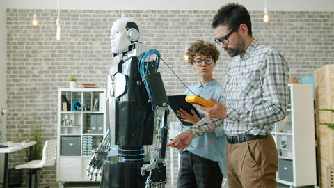Couple of developers testing human-like robot in modern office using tablet Archivo