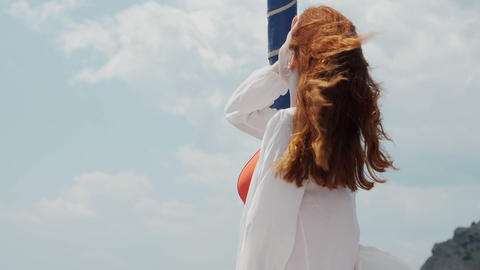 Red haired young woman directs her face to the sun Wind shakes her hair ビデオ