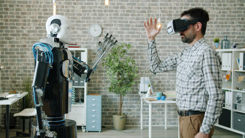 Engineer controlling robot using virtual reality glasses, machine copying Archivo
