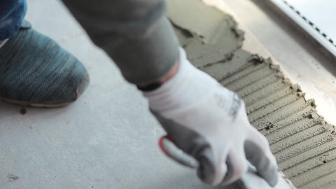 Close look at the constuction worker laying down the tile on cemented floor Live Action