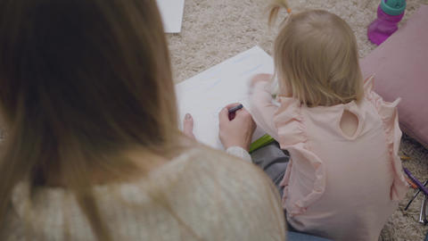 Top view of young Caucasian woman and little baby girl drawing with colorful Footage