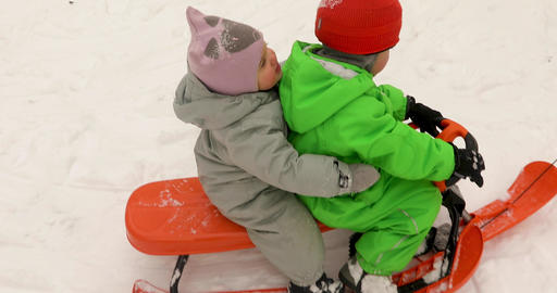 Cute kids in winter clothes riding sled together Archivo