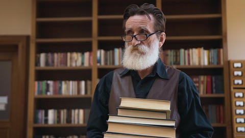 Intelligent senior bearded man holding in his hands a lot of books and coming Archivo
