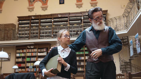 Intelligent senior bearded man telling about library to his cute interested Archivo