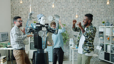 Group of scientists dancing in office with smart human-like robot having fun Archivo