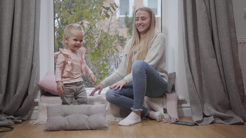 Pretty Caucasian baby girl playing with soft pillows and having fun together Footage