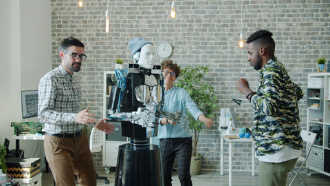 Smart robot dancing with group of happy developers at office business party Archivo