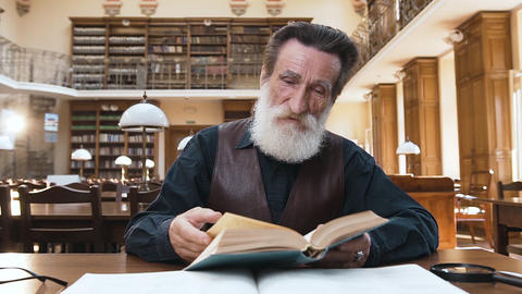 Close up of focused old bearded man which flipping through book pages sitting at Archivo