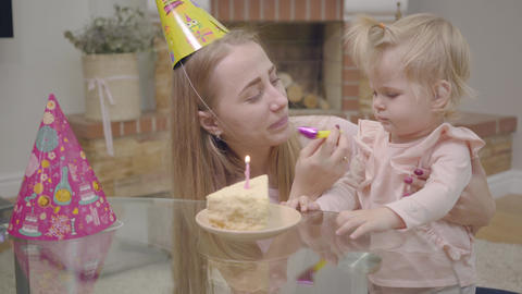 Young Caucasian mother in party hat and little cute baby girl playing with party ビデオ