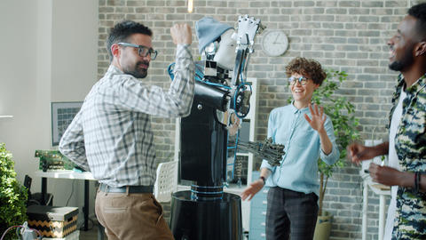 Joyful robotic engineers dancing with intelligent human-like robot in office Archivo