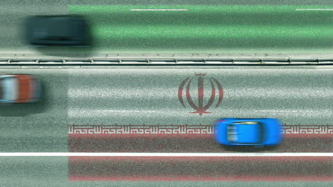 Aerial top down view of cars revealing flag of Iran on the road. Traveling Footage
