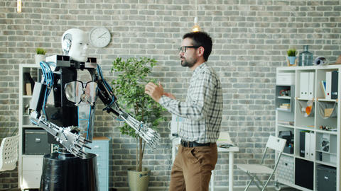 Happy developer dancing in office room with smart robot having fun at work Archivo
