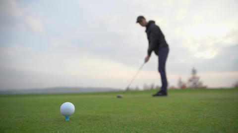 A golf player prepares the ball to be fired at the golf course Archivo