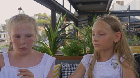 Cute teenage girls making order at outdoors cafe ビデオ