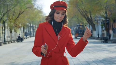 Elegant young girl in a red coat dances freely on the street. It takes pleasure Footage