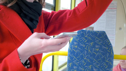 Portrait of an elegant young girl in a red coat. Uses a smartphone in public Footage