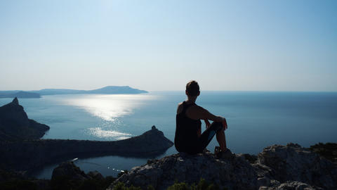 Silhouette of a happy hiker woman sitting and relaxing on the summit. Girl Footage