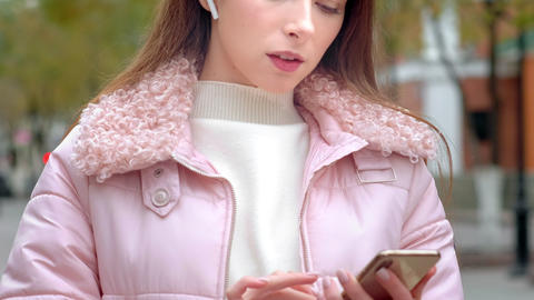 Young beautiful girl makes a call on a smartphone, uses wireless white Live Action
