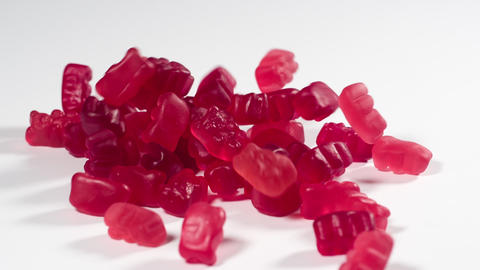 Gummy Bears falling onto a white surface in slow motion Archivo