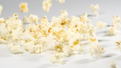 Fresh popcorn falling onto a white surface in slow motion Archivo