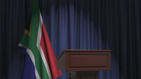 National flag of South Africa and speaker podium tribune. Political event or Live Action