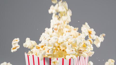 Popcorn falling in slow motion into a popcorn bucket Archivo