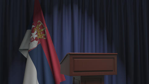 National flag of Serbia and speaker podium tribune. Political event or statement Live Action