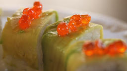 Close-up of sushi rolls decorated with avocado slices and red caviar. Sesame oil Archivo