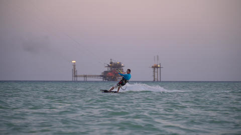 Kite surfer is gliding in Dead Sea on high speed, jumping and holding the board Live Action