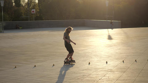 Young long-haired man roller skater is dancing between cones in the evening in a ビデオ