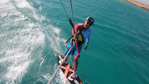 Kite surfer is gliding on high speed and jumping over the ropes, action camera Live Action