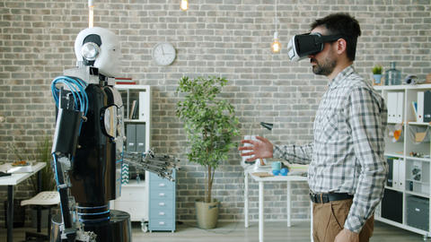Robot copying movements of young scientist in virtual reality glasses in office Live Action