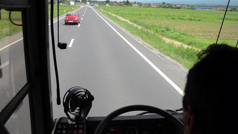 Views over the head of driver through the windshield of a bus traveling at speed Footage